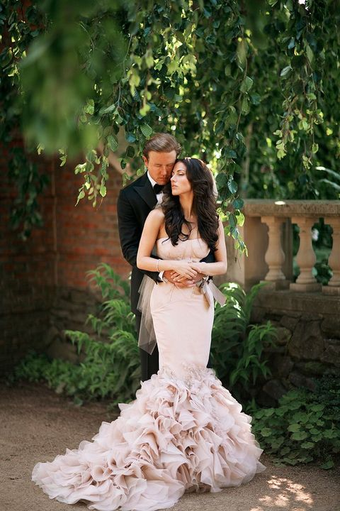a black tuxedo for the groom and a blush mermaid dress for the bride