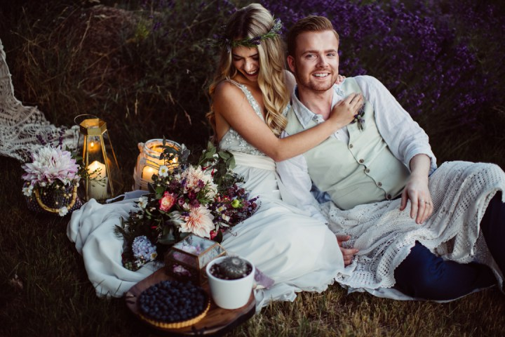 A small picnic setting with candle lanterns and a blueberry tart instead of a traditional wedding cake