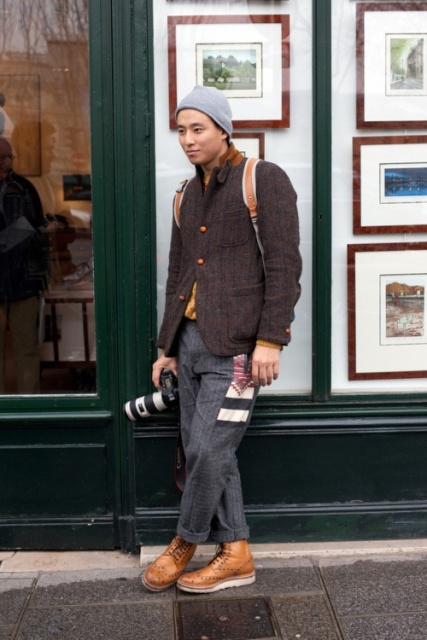 With tweed blazer, gray pants and beanie
