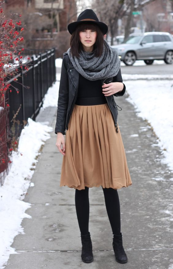 tan knee skirt, a black leather jacket and boots, a grey blanket scarf and a hat