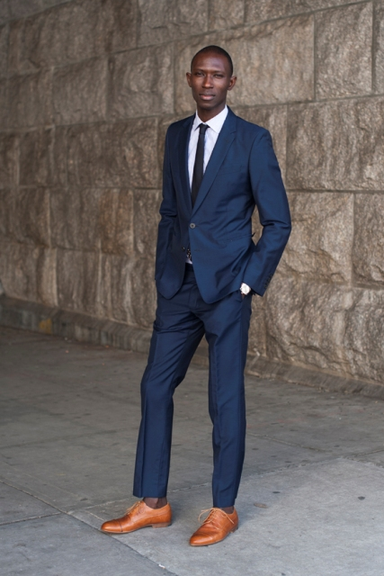 With navy blue suit, white shirt and black tie