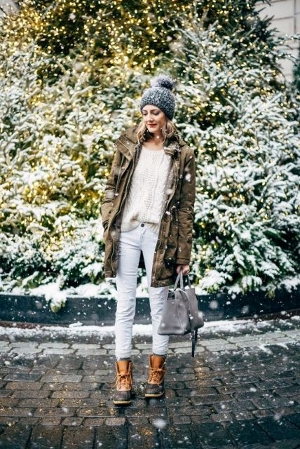 With loose sweater, white pants, parka and gray beanie
