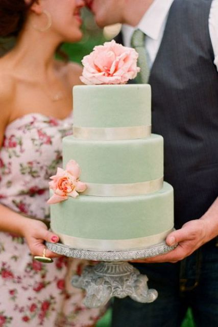 a mint wedding cake with ivory ribbon and fresh peach flowers