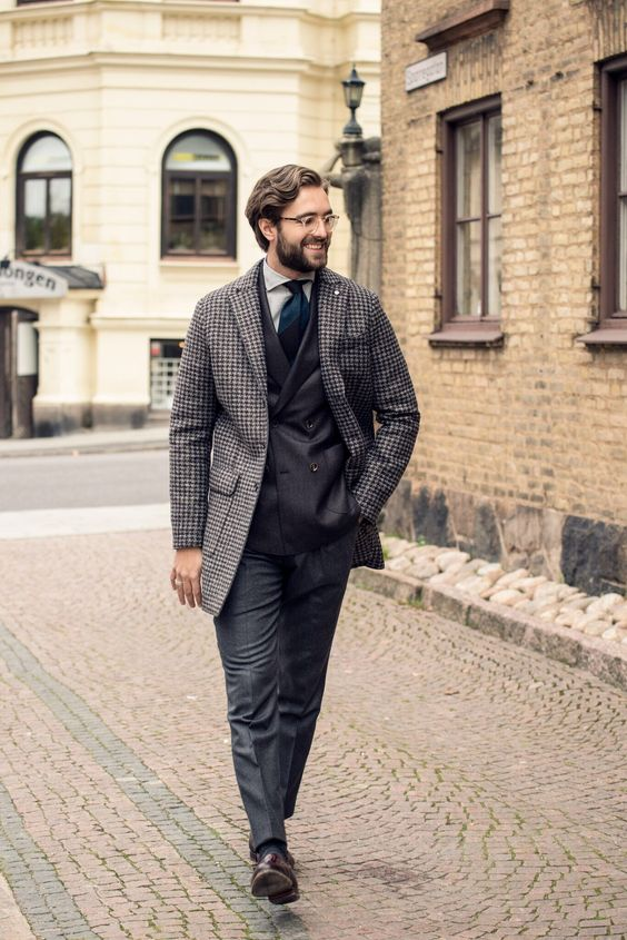 vintage-inspired look with a black suit, a tweed coat and a tie