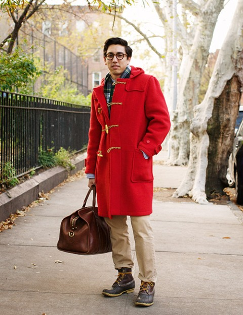 With plaid shirt, red duffle coat, camel pants and leather bag