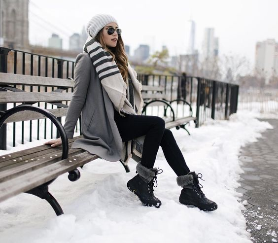 fur boots, black leggings, a grey coat, a scarf and a beanie