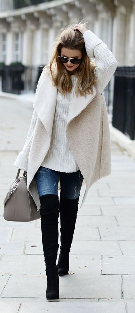 black knee-length boots, jeans, a white chunky knit sweater and a white coat