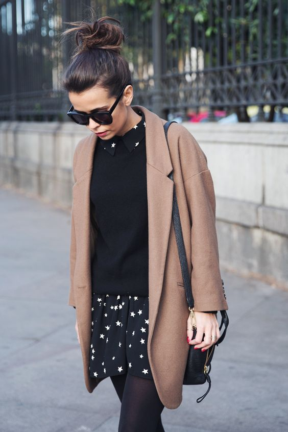 a black sweater, a star printed dress and a camel coat