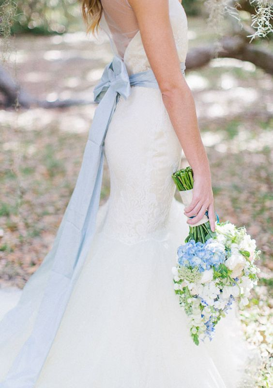 pale blue sash with a bow and corresponding flowers