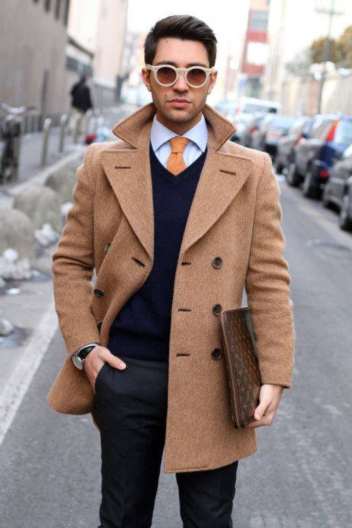 a smart casual look wwith a peach coat and tie, a navy sweater and black pants
