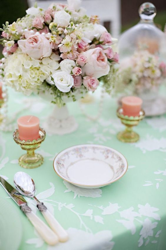mint tablecloth with white lace, peach candles and flowers