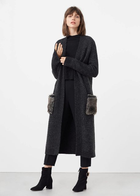 With black shirt, crop trousers and mid calf boots