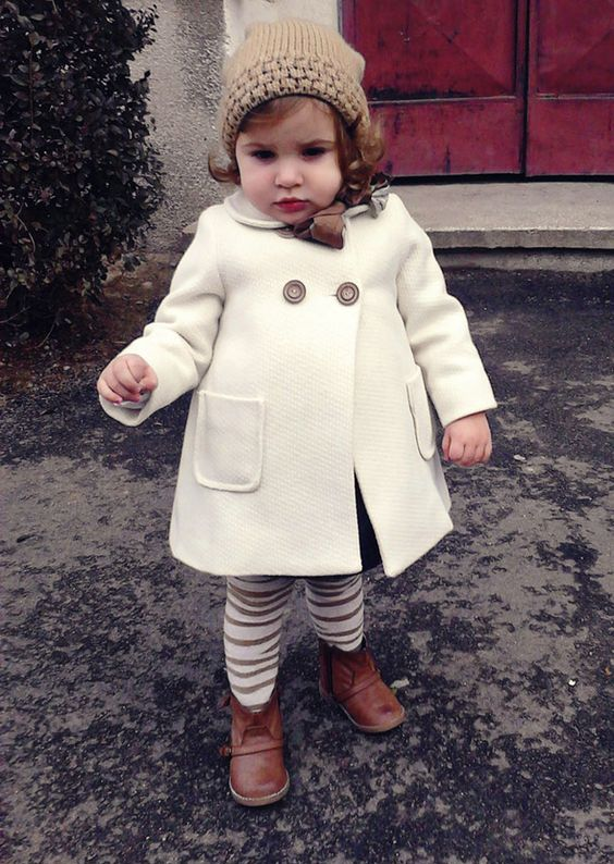 a white coat, striped leggings, a beanie and boots