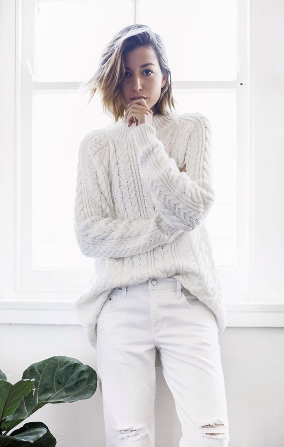 a white cable knit sweater and ripped denim