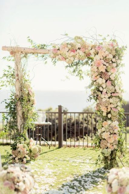 rustic wedidng arch with lush florals in ivory and pink shadeds