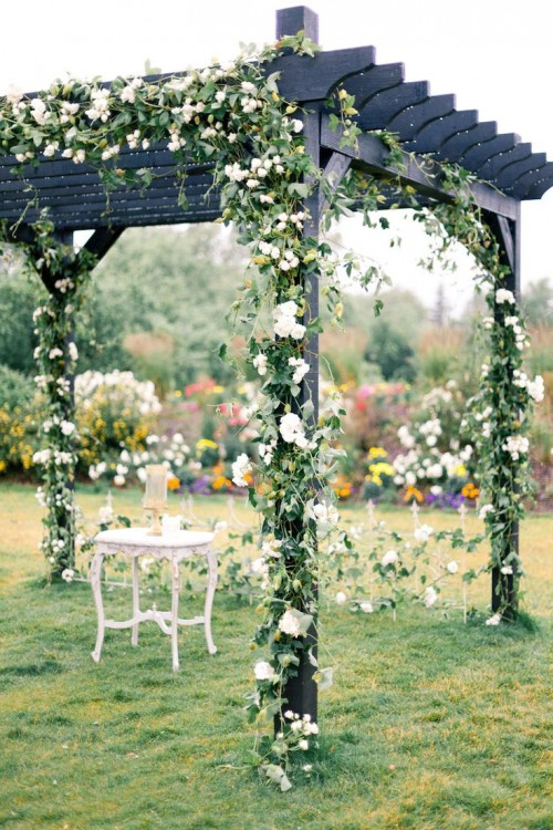 dark wedding arch all intewoven with greener and white blooms
