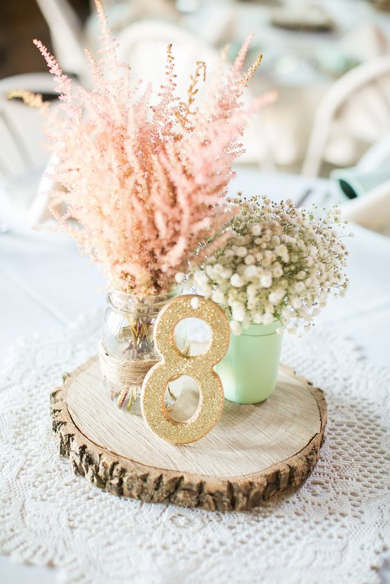 wood slice with a glitter table number, mason jars with flowers