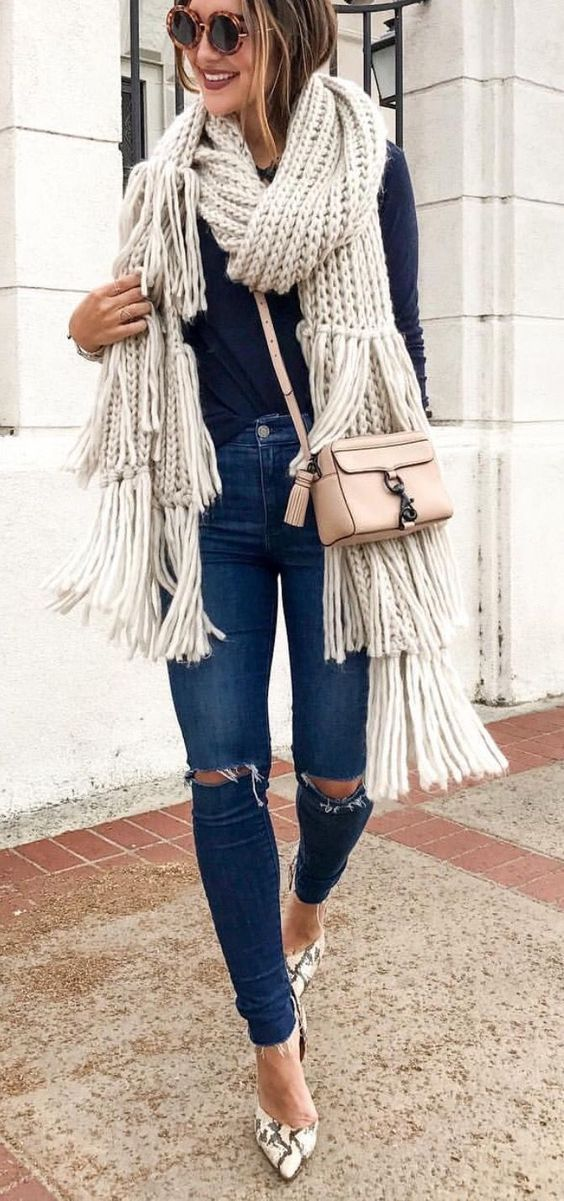 ripped blue jeans, a navy top, snake skin print shoes and a chunky knit scarf