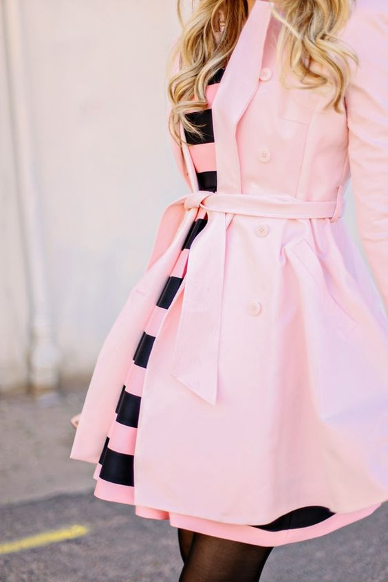 a pink and black striped dress and a pink coat over it