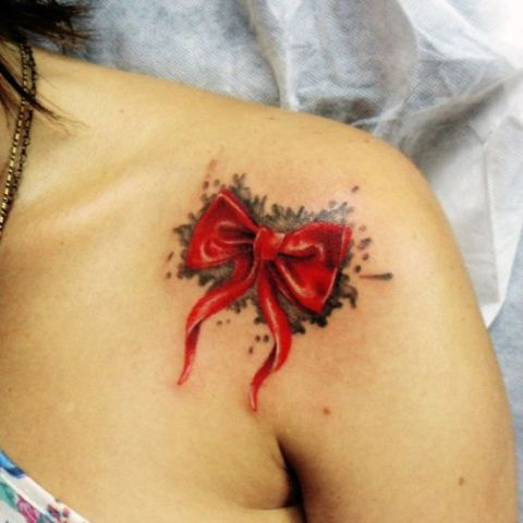 Watercolor red bow tattoo on the shoulder