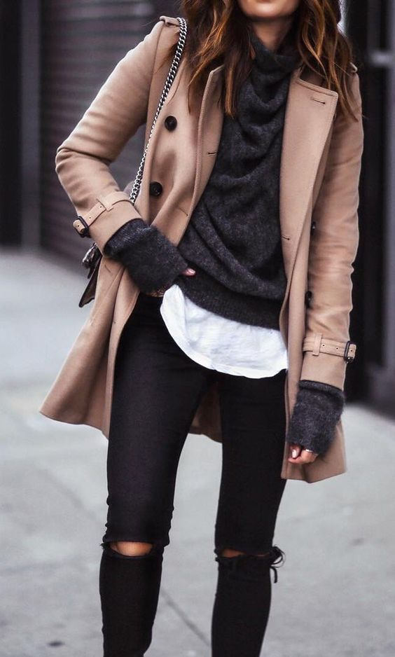 a short ocher coat, a black sweater and a white tee