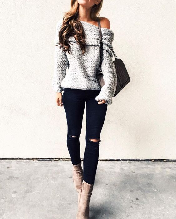 black ripped jeans, light brown suede boots, a grey off the shoulder sweater