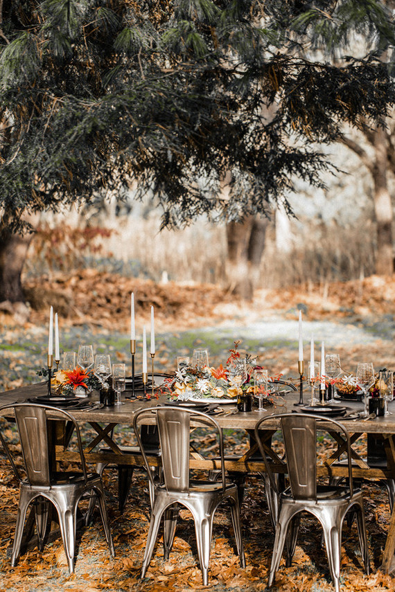 The metal table and chairs were decorated with candles, flal leaves and flowers