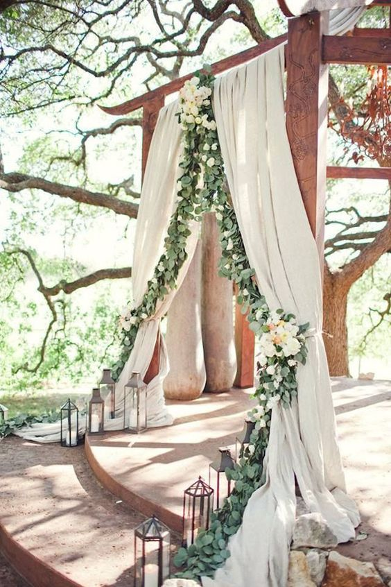 ceremony spot decorated with curtains and eucalyptus garland and neutral florals