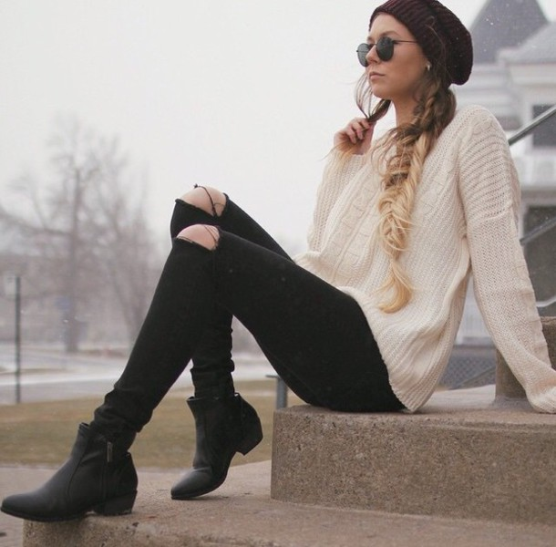 ivory oversized swetaer, a burgundy beanie, ripped jeans and boots