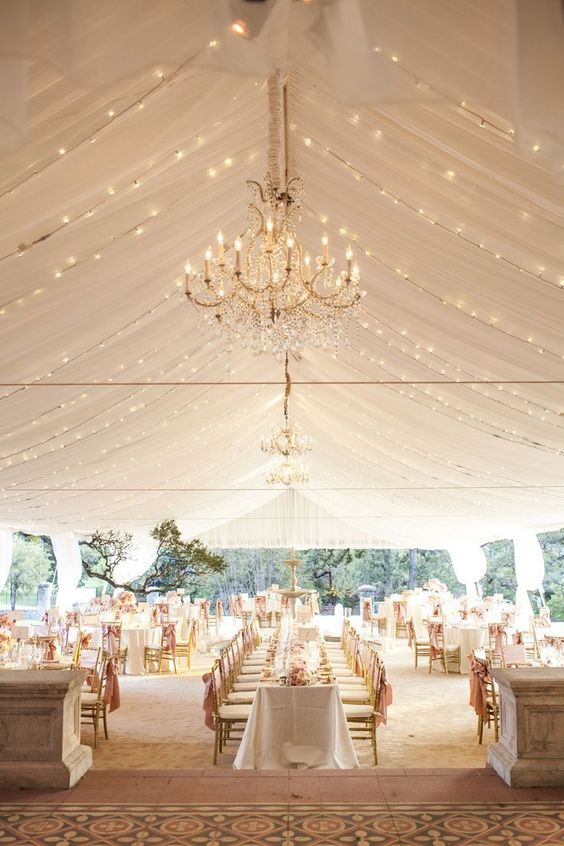 neutral wedding tent with a lot of lights and chandeliers