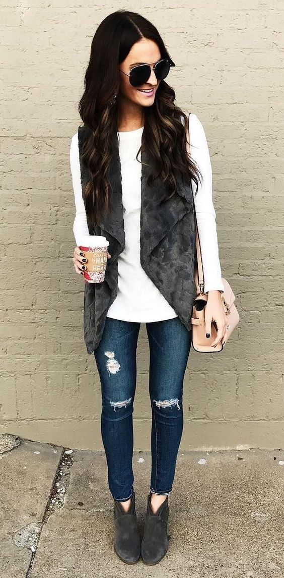 ripped fitted jeans, a white sweater, a faux fur vest and suede ankle booties