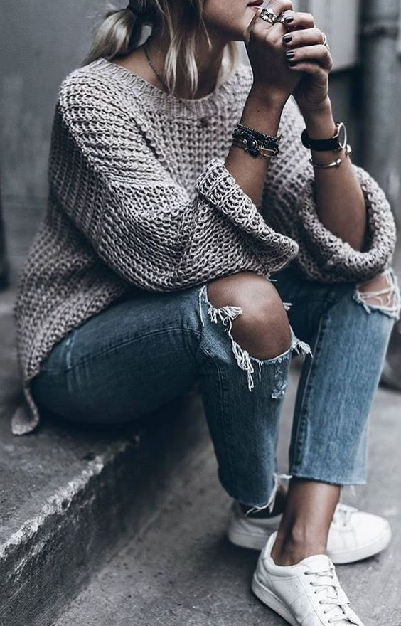 ripped jeans, a chunky knit oversized sweater and white sneakers