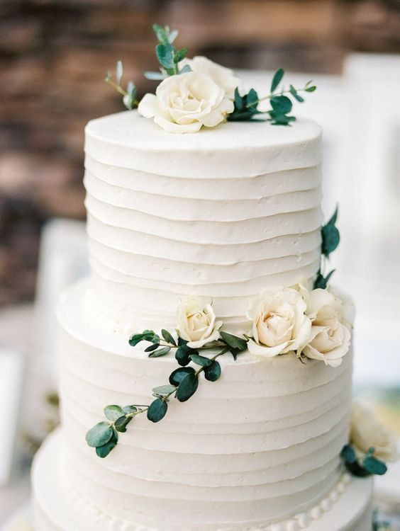 simple white cake decorated with greenery and neutral flowers