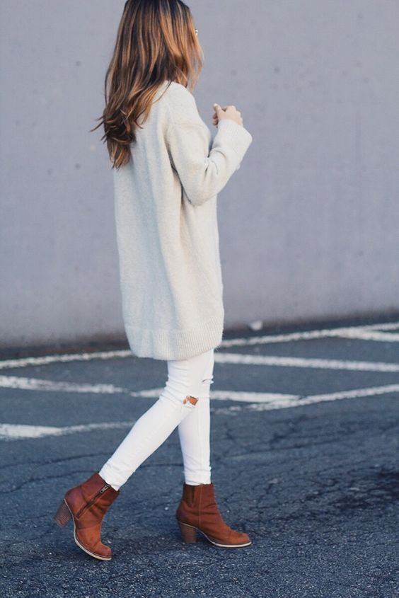 white ripped jeans, an oversized white sweater and brown ankle boots