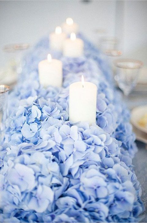 pale blue hydrangeas create a lush bed for placing a row of candles