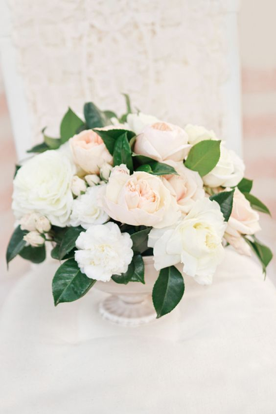 cream and blush flower centerpiece with green leaves