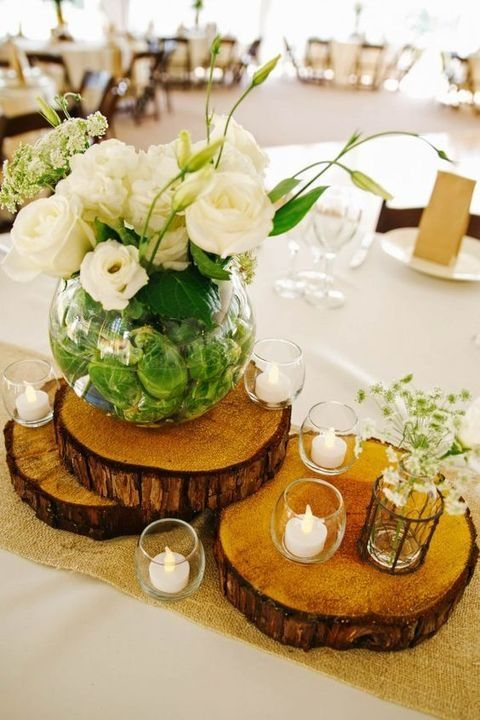 wood slices with candle holders and a large vase with white florals