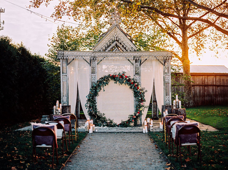 This gorgeous oversized wreath backdrop of greenery and flowers looks unforgettable
