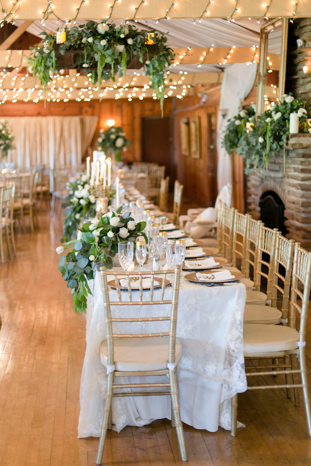 Long head table with white, green, and gold decor | Leah Marie Photography