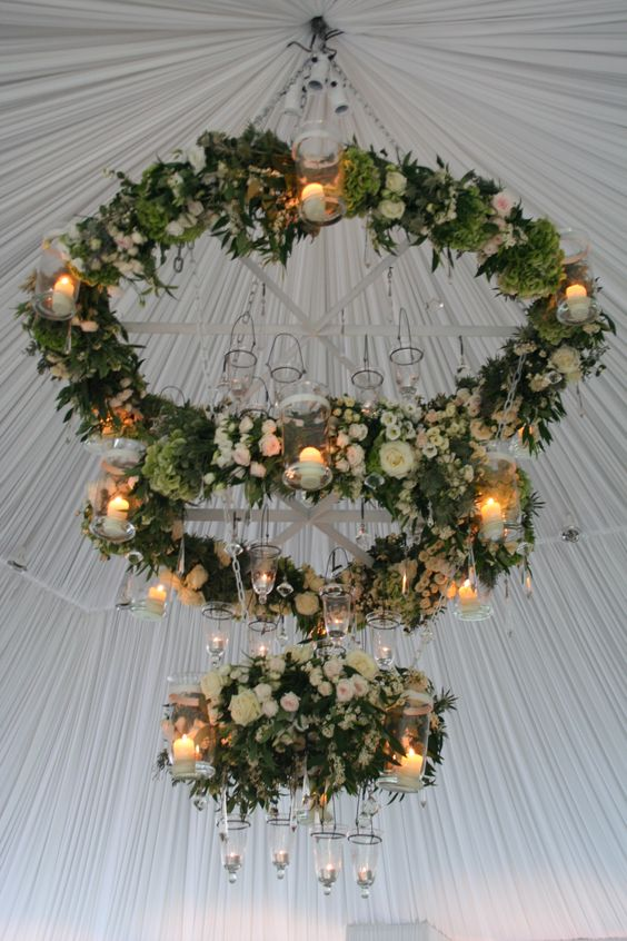 a trio of floral chandeliers with greenery and candle holders