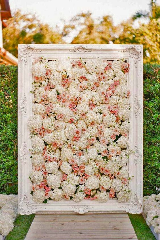 framed ivory and peach pink flower wall as a wedding backdrop