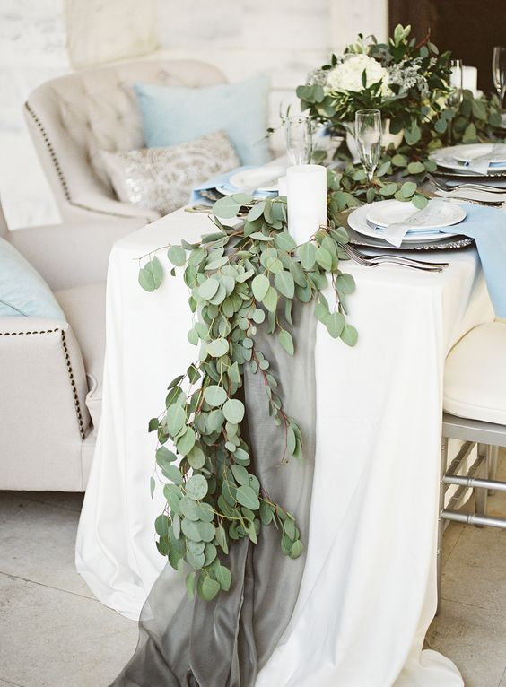 fabric table runner and a eucalyptus garland over it look very delicate