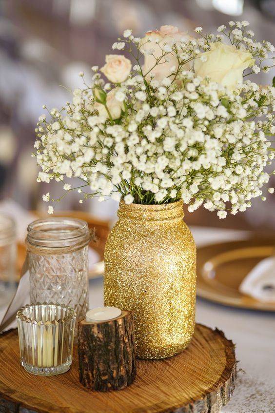 woodland centerpiece with a glitter mason jar, wood piece candle holder and flowers