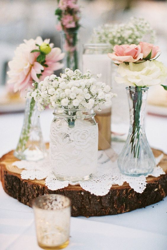 wood slice with doilies, mason jars and bottles with flowers