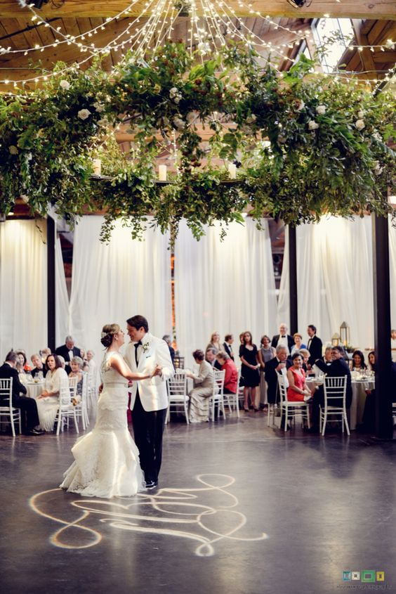 oversized leafe chandelier with some white roses over the dance floor