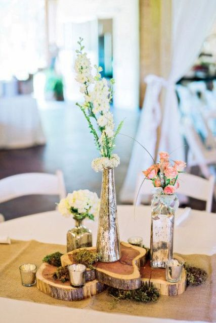 eye-catchy centerpiece with several wood slices and mercury vases