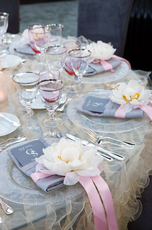 light grey tablescape with a ruffled tablecloth and pink glasses and ribbon