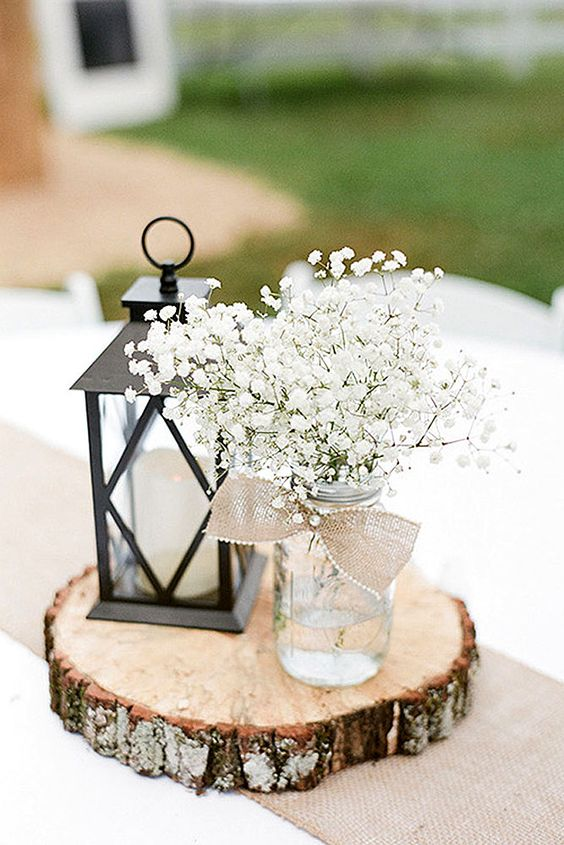 stylish centerpiece with a candle lantern and a mason jar with baby