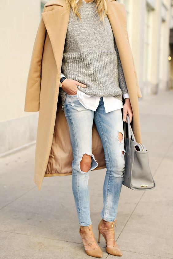 ripped jeans, lace up heels, a grey sweater over a shirt and a camel coat