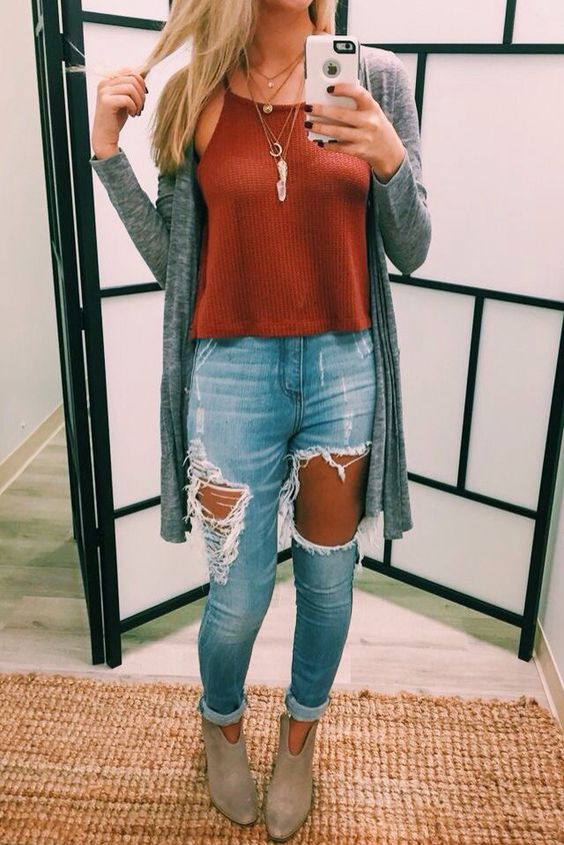 ripped jeans, a red top, a grey cardigan and ankle booties